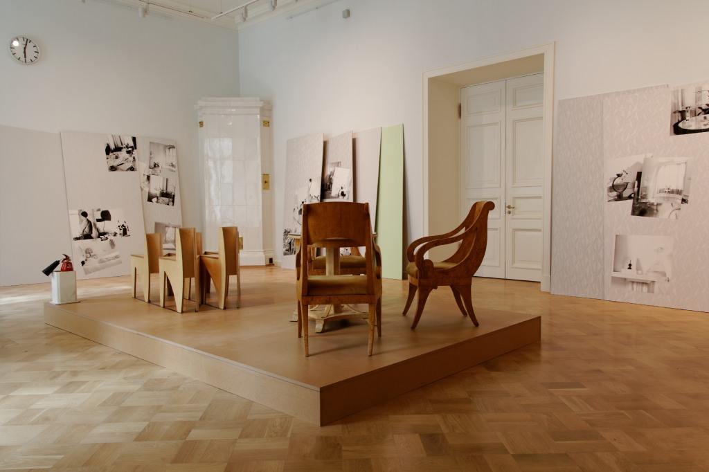Marc Camille Chaimowicz Installation view, MANIFESTA 10, General Staff Building, State Hermitage Museum. Pictured: Here and There 1978 Plywood, acrylic paint, black and white photographs, text, 17 parts Each part 244 × 122 × 1.3 cm; total dimensions variable Courtesy the artist and Cabinet Gallery, London Seating for Raven Row 2010 5 seats, birch plywood and steel 83 × 120 × 170 cm Courtesy the artist and Cabinet Gallery, London Marc Camille Chaimowicz Vase 2014 Porcelain 28 × 17 cm Courtesy the artist and Cabinet Gallery, London