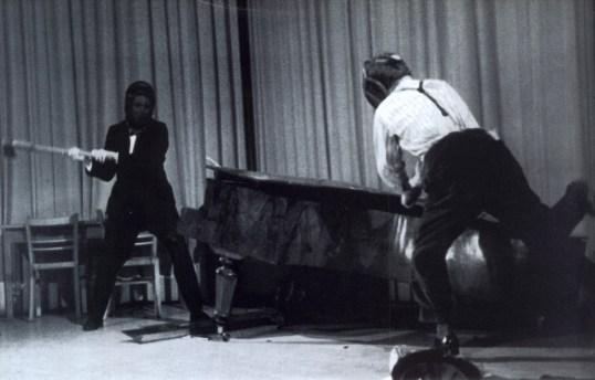 """Das 2. literarische cabaret der Wiener Gruppe. In der Nummer """"2 welten"""" zertrümmern Friedrich Achleitner und Gerhard Rühm ein Klavier auf der Bühne. Wien. Photographie. 1959"""